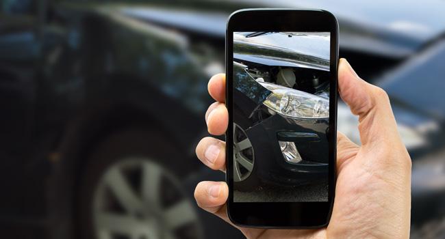 Un agente dell'assicurazione fotografa un incidente con il suo telefono.