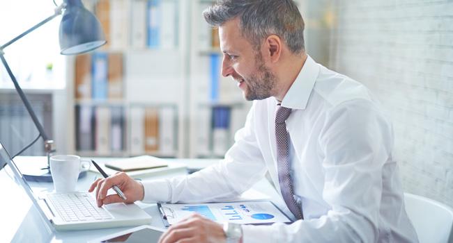 Un assicuratore sorridente osserva i grafici sulla sua scrivania