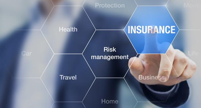 Un uomo indica uno schermo su cui compaiono le parole Assicurazione, Gestione dei rischi e Viaggio