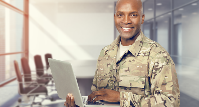 Solider holding laptop and smiling